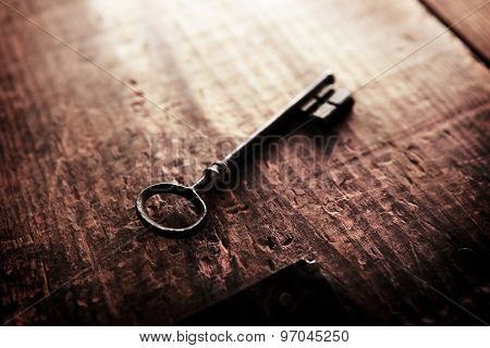 An vintage key on an grungy old wooden surface incoming light. Shallow depth of field.