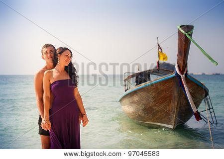 Girl And Guy Hug Against Longtail Boat