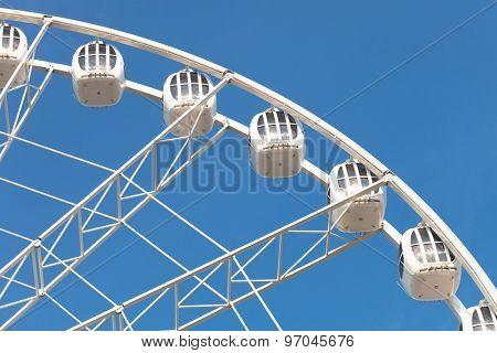 part of white ferris wheel against blue sky background