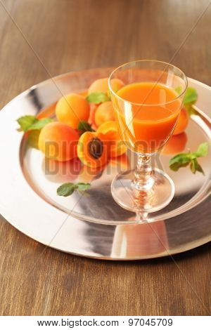 Glass of apricot juice and fresh fruits on table close up
