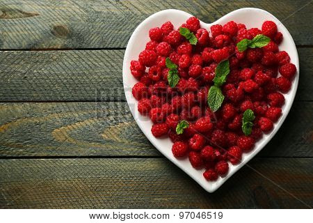 Sweet raspberries on plate, on wooden  background