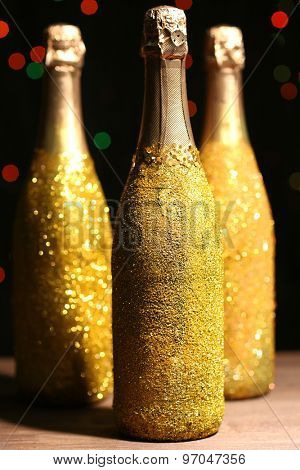 Decorative champagne bottles on dark colorful spotted background