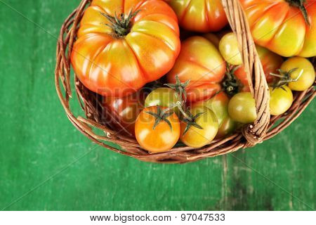 Green tomatoes in basket on table close up