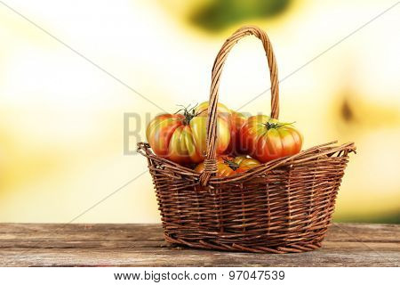 Green tomatoes in basket on bright background