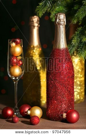 Decorative champagne bottles on wooden table, closeup