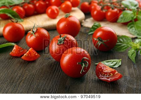 Fresh tomatoes with basil on wooden table close up