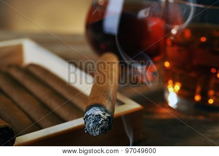 Cigars and burning one with cognac on wooden table, closeup