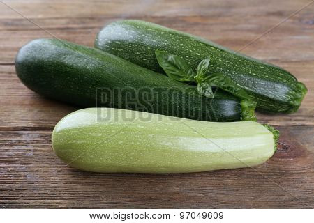 Fresh zucchini with squash and basil on wooden background