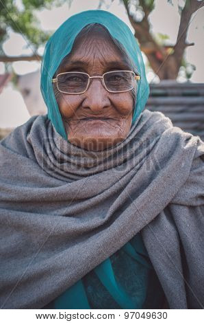 GODWAR REGION, INDIA - 14 FEBRUARY 2015: Elderly Indian woman in glasses with headscarf and blanket around shoulders. Post-processed with grain, texture and colour effect.