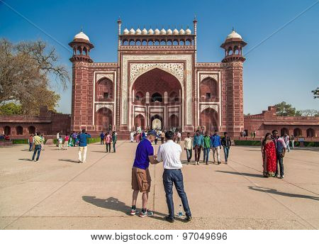 AGRA, INDIA - 28 FEBRUARY 2015: South side of Great Gate in Taj Mahal area with tourist and guide preparing to take a photo.