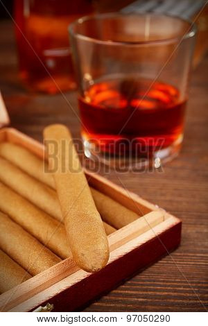 Cigars in humidor with cognac on wooden table, closeup