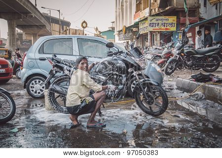 MUMBAI, INDIA - 16 JANUARY 2015: Young Indian boy hand washes motorbike in dirty parking space. Bike is soaked in soap. Post-processed with grain, texture and colour effect.