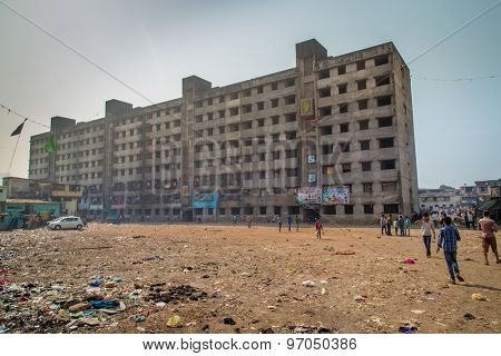 MUMBAI, INDIA - 12 JANUARY 2015: Unfinished empty apartment block and dirty field with people in Dharavi slum. Dharavi is one of the largest slums in the world.