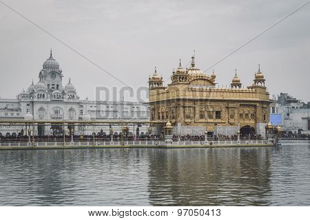 AMRITSAR, INDIA - 01 MARCH 2015: Pilgrims at Golden Temple, the holiest Sikh gurdwara in the world. Post processed with texture and grain.