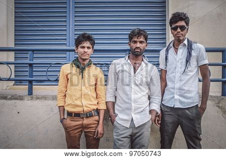 KAMALAPURAM, INDIA - 02 FABRUARY 2015: Three indian youngsters stand on a marketplace close to Hampi. Post-processed with grain, texture and colour effect.