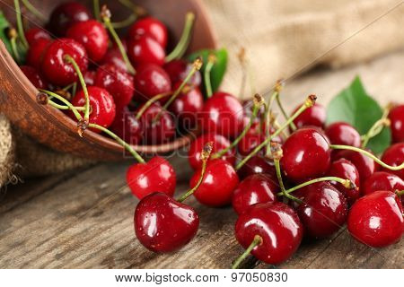 Fresh cherries in bowl on wooden table with sackcloth, closeup