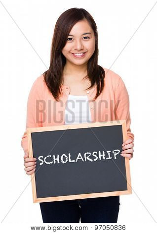 Asian woman with black board showing a word scholarship
