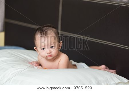 Unhappy Cute Asian Baby Lying On A White Pillow, On Bed