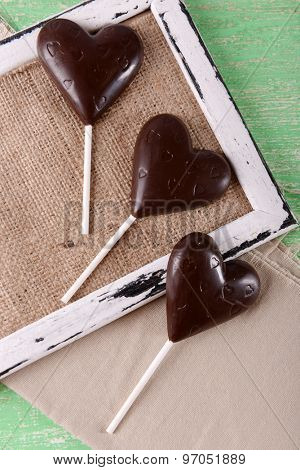 Chocolate heart shaped candies on sticks on sackcloth, closeup