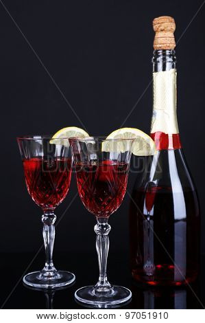 Glasses of champagne with slices of lemon on black background