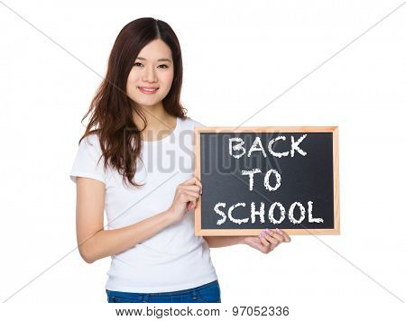 Woman with the chalkboard showing phrase of back to school