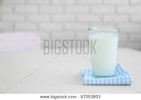 Glass of milk on wooden table, on bricks wall background
