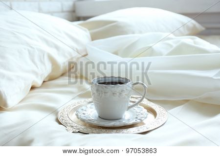 Morning cup of coffee on comfortable bed in bedroom