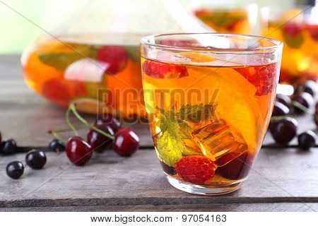 Punch with berries in glassware on wooden table, closeup