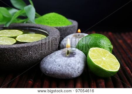 Spa still life in green color on bamboo mat on dark background
