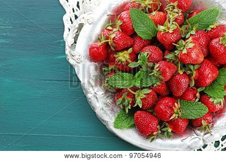 Red ripe strawberries on tray, on color wooden background