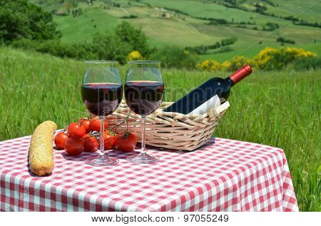 Red wine, bread and tomatoes on the chequered cloth against Tuscan landscape. Italy