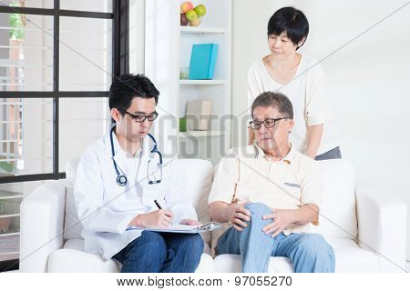 Doctor and patient. Asian old man consult family doctor, sitting on sofa. Senior retiree indoors living lifestyle.