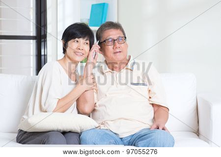 Modern technology, age and people concept. Mature Asian couple using smart phone. Family living lifestyle at home.