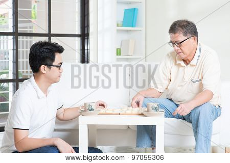 Chinese family playing Chinese chess (Xiang Qi) at home, senior father and adult son.