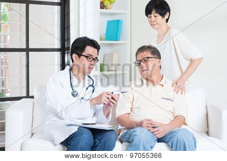Doctor and patient healthcare concept. Asian elder man consult family doctor, sitting on sofa. Senior retiree indoors living lifestyle.