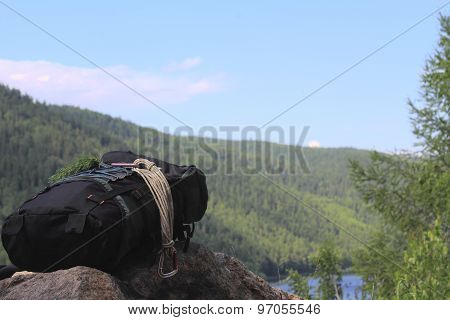 A Backpack With A Rope Are On A Cliff High Above The Lake