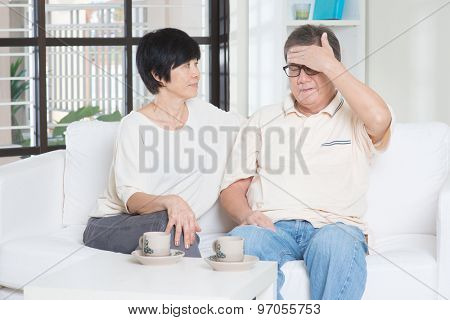 Portrait of mature Asian man having headache, sitting on sofa with wife at home, senior retiree indoors living lifestyle.