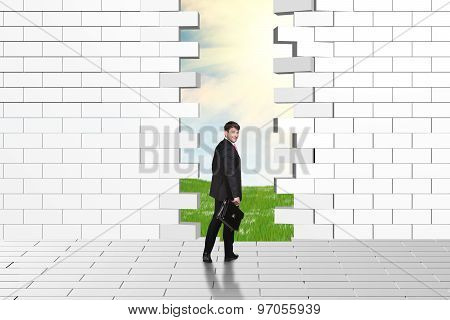 Beautiful businessman watching dilapidated brick wall