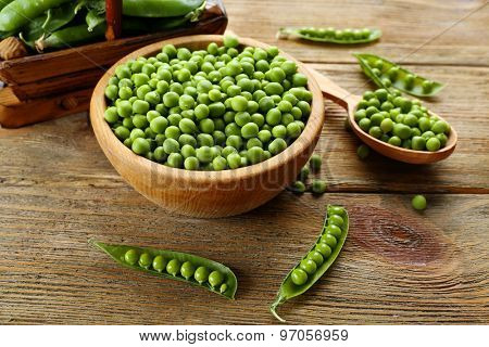 Fresh green peas in bowl and spoon on table close up