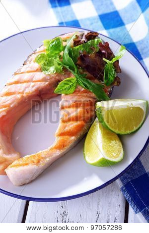 Tasty grilled salmon with greens on table close up