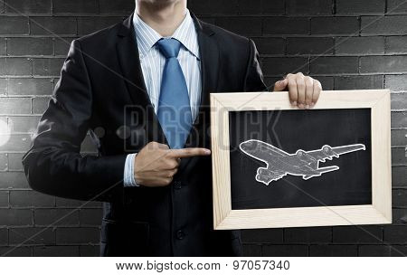 Close up of businessman holding wooden frame with airplane sign