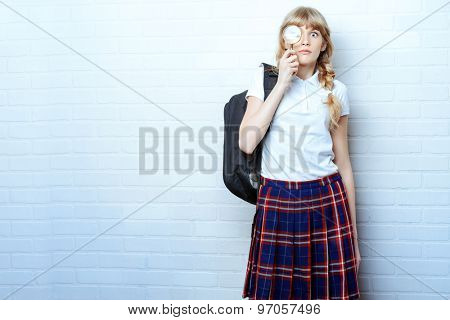 Cute teen girl in school uniform looking through a magnifying glass. Education. Studio shot.