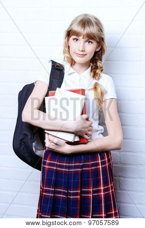 Pretty teen girl wearing school uniform and school bag. Education. Studio shot.