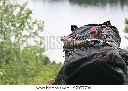 Backpack, Mug Of Tea And A Flower Lying On A Cliff Above The Lake