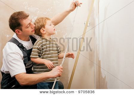 Father and son measuring dry wall