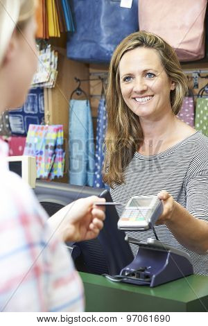 Shopper Paying For Goods Using Credit Card Machine