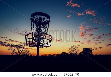 Silhouette Of Disc Golf Basket Against Sunset