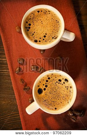 Cups of coffee on napkin on table close up