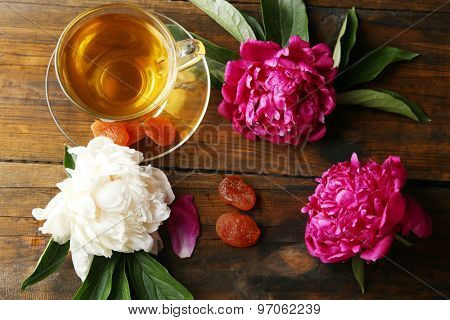 Composition with cup of herbal tea and peony flowers on wooden background