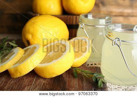 Still life with lemon juice and sliced lemons on wooden table, closeup
